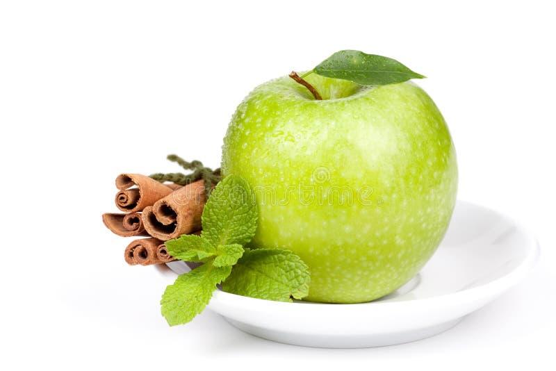 Ein reifer grüner Apple mit Minze und Zimt auf Platte lizenzfreie stockfotos