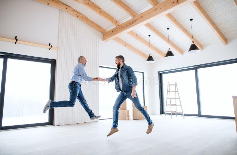 Ein reifer Mann, der mit seinem älteren Vater im neuen Haus, ein neues Hauptkonzept springt lizenzfreies stockfoto