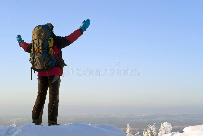 Ein Reisender auf einen Winterberg bewundert die Landschaft stockbild