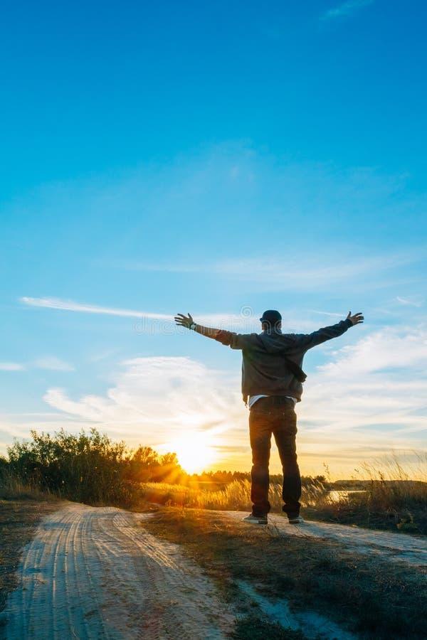 Ein Reisender auf Landstraße während des Sonnenuntergangs stockfotos