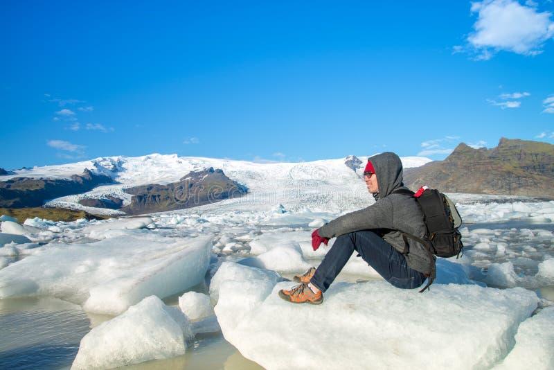Ein Reisender, der auf kleinem Eis an der Fjallsarlon-Gletscher-Lagune in S?dost-Island sitzt stockfoto