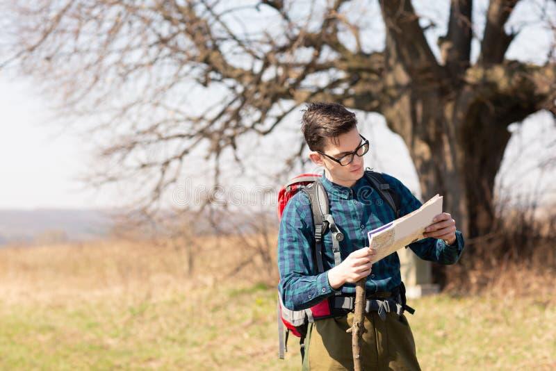 Ein Reisender mit einem Rucksack, die Karte betrachtend und gehen in die Landschaft Baum im Hintergrund stockfoto