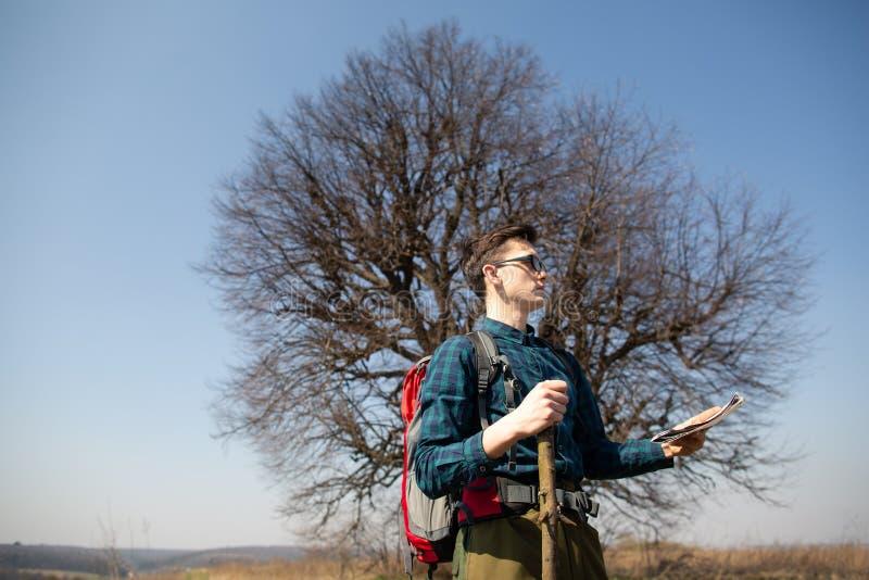 Ein Reisender mit einem Rucksack, die Karte betrachtend und gehen in die Landschaft Baum im Hintergrund lizenzfreies stockbild