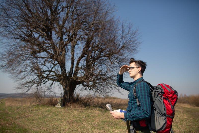 Ein Reisender mit einem Rucksack, die Karte betrachtend und gehen in die Landschaft Baum im Hintergrund stockbilder
