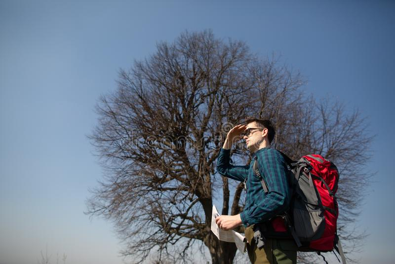 Ein Reisender mit einem Rucksack, die Karte betrachtend und gehen in die Landschaft Baum im Hintergrund lizenzfreie stockfotos