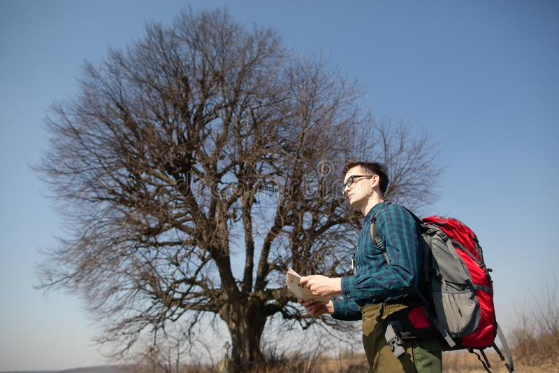 Ein Reisender mit einem Rucksack, die Karte betrachtend und gehen in die Landschaft Baum im Hintergrund stockbild