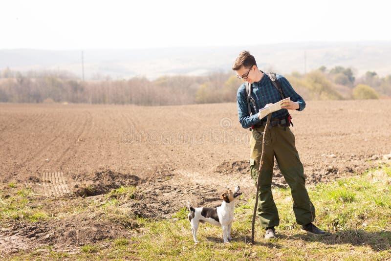 Ein Reisender mit einem Rucksack und seinem Hund, die Karte betrachtend und gehen in die Landschaft stockfotografie