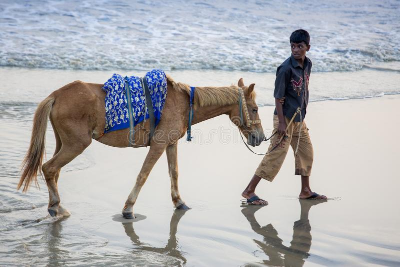 Ein Reitenjunge, der ihre Kunden auf Patenga-Strand, Chittagong, Bangladesch sucht stockbilder