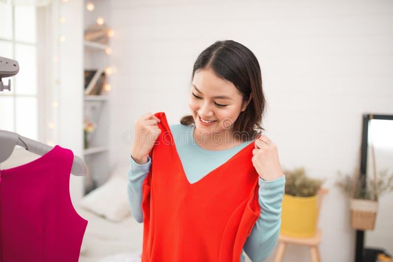 Ein reizendes asiatisches Mädchen, das zu Hause auf neuem Kleid versucht lizenzfreie stockfotos
