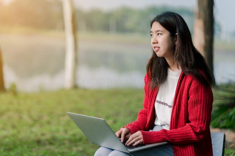 Ein reizendes asiatisches M?dchen ist im touristischen Bereich hell Es gibt eine Laptop-Computer in der Hand auf der Stra?e unter stockbilder