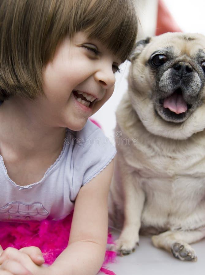 Ein reizendes entzückendes junges Kind mit Pug lizenzfreies stockfoto