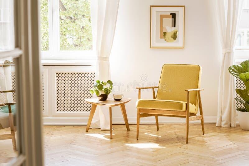 Ein Retro-, gelber Lehnsessel und ein Holztisch in einem schönen, sunn stockfotografie