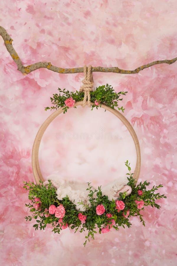 Ein Ring von grünen Zweigen und von rosa Rosen hängt an einer Niederlassung, für Fotos von neugeborenen Babys lizenzfreie stockfotografie