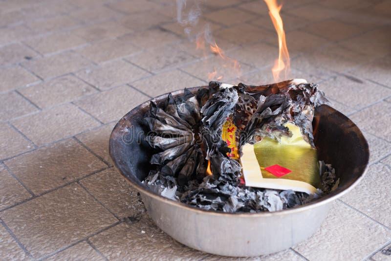 Ein Ritual, zum des goldenen Papiers zum Vorfahr zu brennen, um Respekt zu zahlen und chinesisches neues Jahr zu feiern stockfotografie