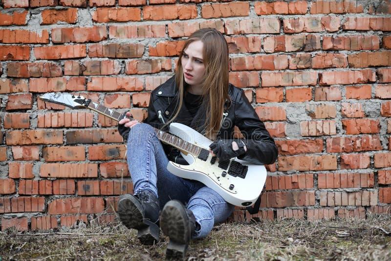 Ein Rockmusikermädchen in einer Lederjacke mit einer Gitarre stockbilder