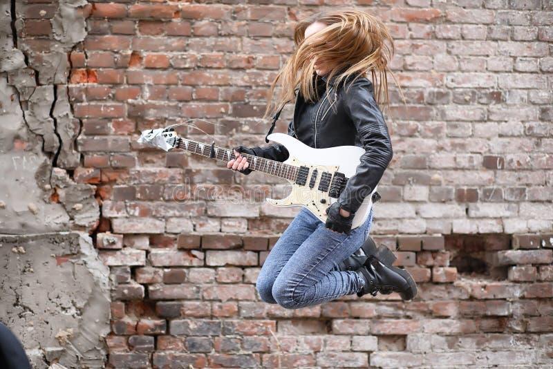 Ein Rockmusikermädchen in einer Lederjacke mit einer Gitarre stockfotos