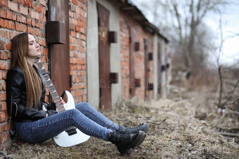 Ein Rockmusikermädchen in einer Lederjacke mit einer Gitarre lizenzfreies stockbild