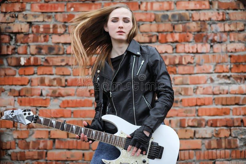 Ein Rockmusikermädchen in einer Lederjacke mit einer Gitarre stockfoto
