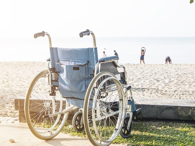 Ein Rollstuhl sitzt auf dem Strand stockfotografie