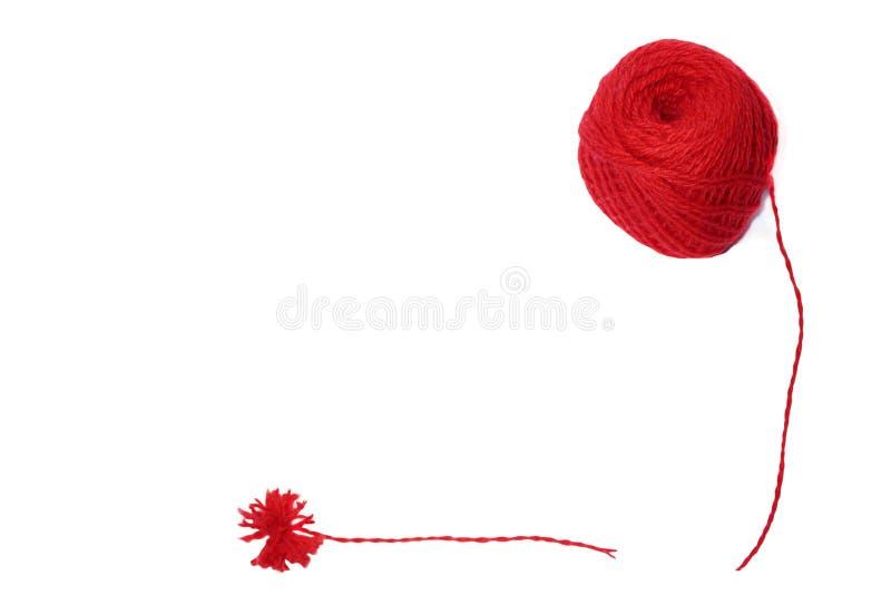Ein roter Ball des Wollgarns für das Stricken und des roten Quasts gemacht vom Garn auf einem weißen Hintergrund stockbilder