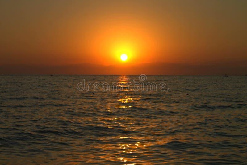 Ein roter, brennender Sonnenuntergang über dem Meer lizenzfreies stockbild
