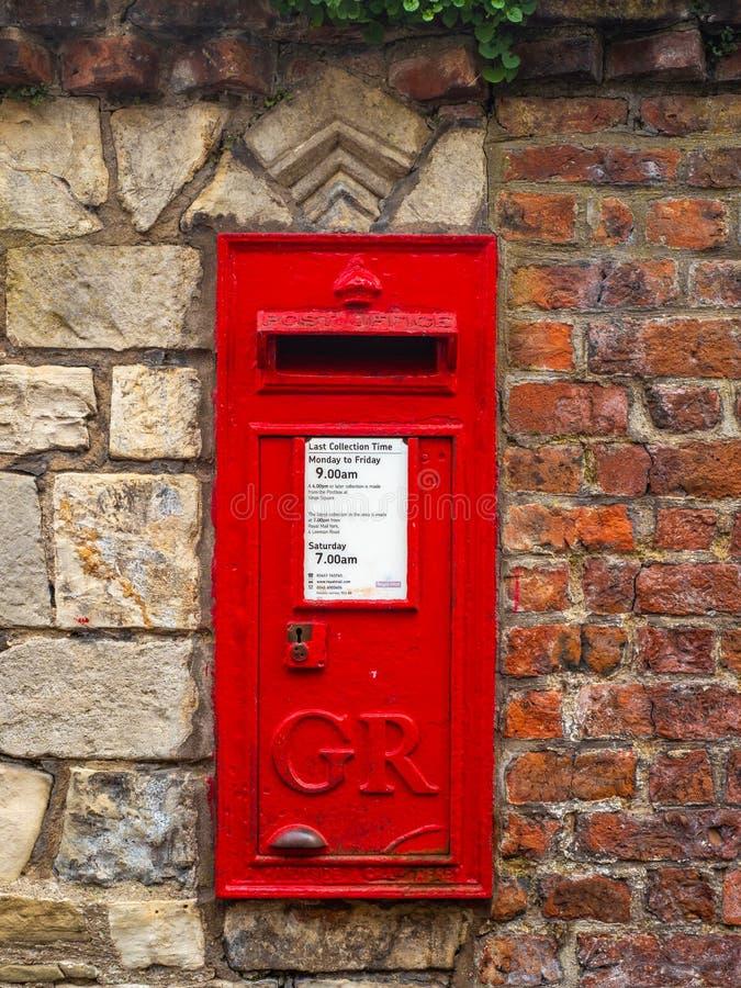 Ein roter britischer Briefkasten in einer Wand stockfoto