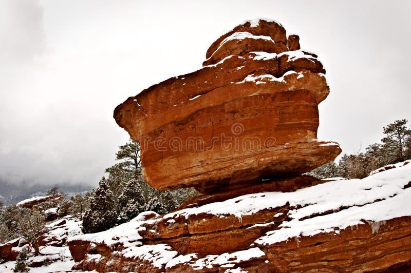 Ein roter Flussstein ist auf einem Berg in einer Szene des verschneiten Winters ausgeglichen lizenzfreies stockbild