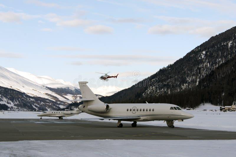 Ein roter Hubschrauber, der über zwei Privatjets im Flughafen von St. Moritz Switzerland im Winter fliegt stockfotos