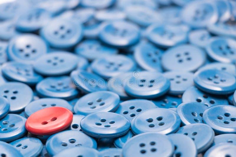 Ein roter Knopf auf einem Haufen von blauen Knöpfen verließ basiert stockfoto