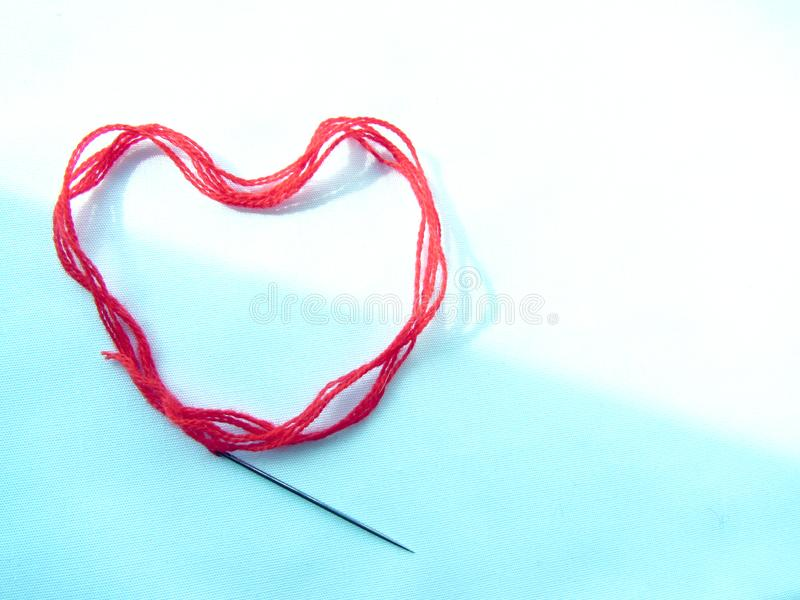 Ein roter woolen starker Faden mit einer Nähnadel liegt in Form eines Herzens, beleuchtet auf dem weißen und blauen Hintergrund lizenzfreies stockfoto