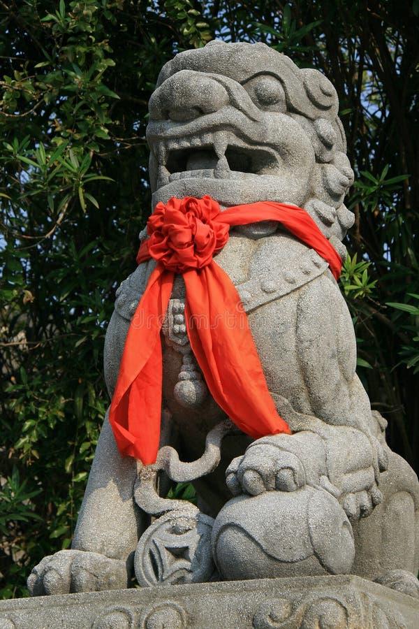Ein rotes Band wurde um die Statue eines Löwes geknotet, der installiert war in den Hof eines buddhistischen Tempels in Hoi An (V stockfotos