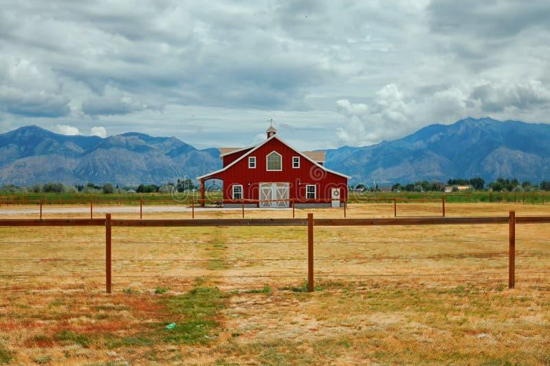 Ein rotes Bauernhaus in einem Tal mit Rocky Mountains im Hintergrund stockfoto