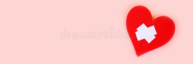 Ein rotes Filzherz gebrochen in zwei Hälften, zusammen geklebt durch einen Gips auf einem rosa Hintergrund stockbild