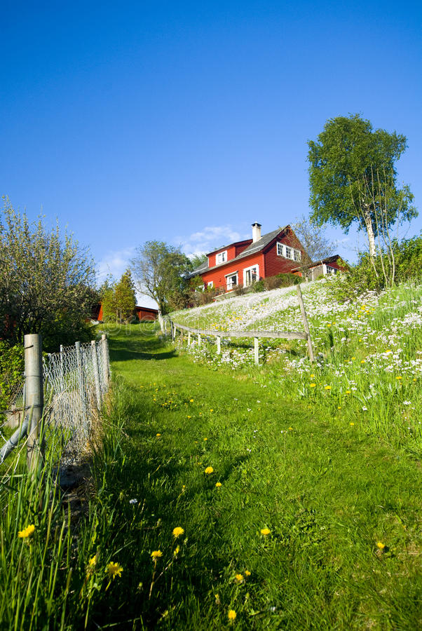 Ein rotes Haus auf dem Grashügel stockfotografie