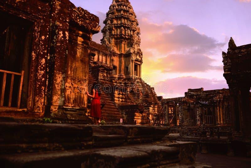 Ein rotes Kleidermädchen, das beim alten Angkor Wat anstarrt stockfotos