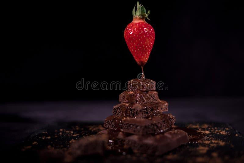 Ein rotes straberry auf einer dunklen Schokolade lizenzfreies stockfoto