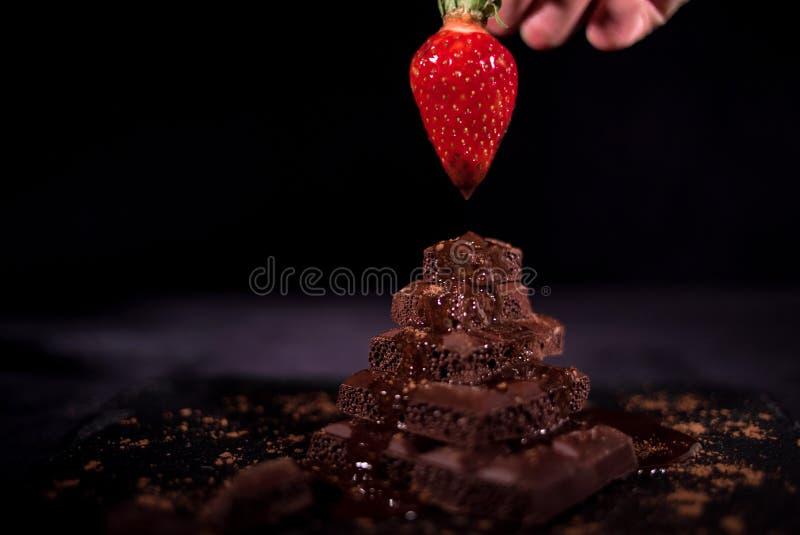 Ein rotes straberry auf einer dunklen Schokolade lizenzfreie stockfotos