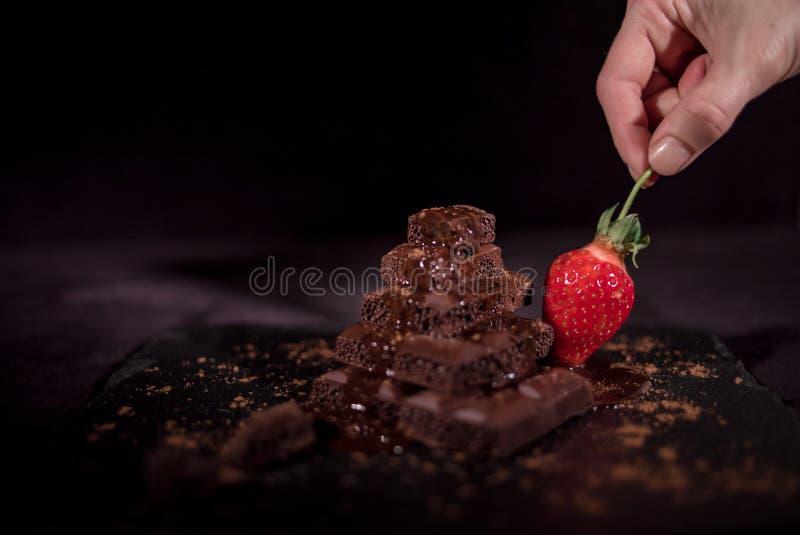 Ein rotes straberry auf einer dunklen Schokolade lizenzfreie stockbilder