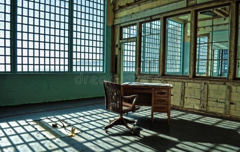 Ein ruinierter Schreibtisch und ein Stuhl in einer verlassenen Gefängnisanlage stockfotografie