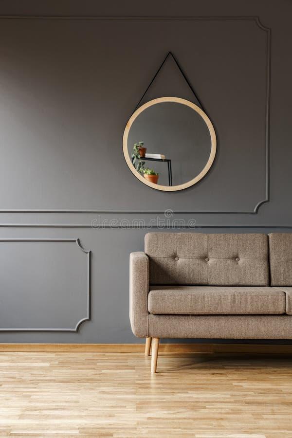 Ein runder Spiegel über einem einfachen, eleganten braunen Sofa und ein Platz für eine Seitentabelle in einem fantastischen Wohnz stockfotos