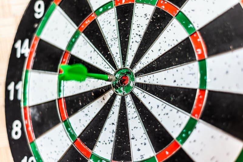 Ein rundes Brett für Pfeile nah spielen oben, ein grüner Pfeil schlug das Ziel lizenzfreie stockbilder