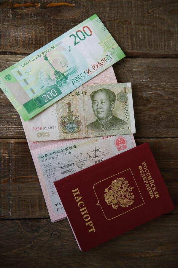 Ein russischer Pass mit einem chinesischen Visum und einem Geld ist ein Yuan und 200 russische Rubel Sichtvermerk, Pass Ferien un lizenzfreies stockbild