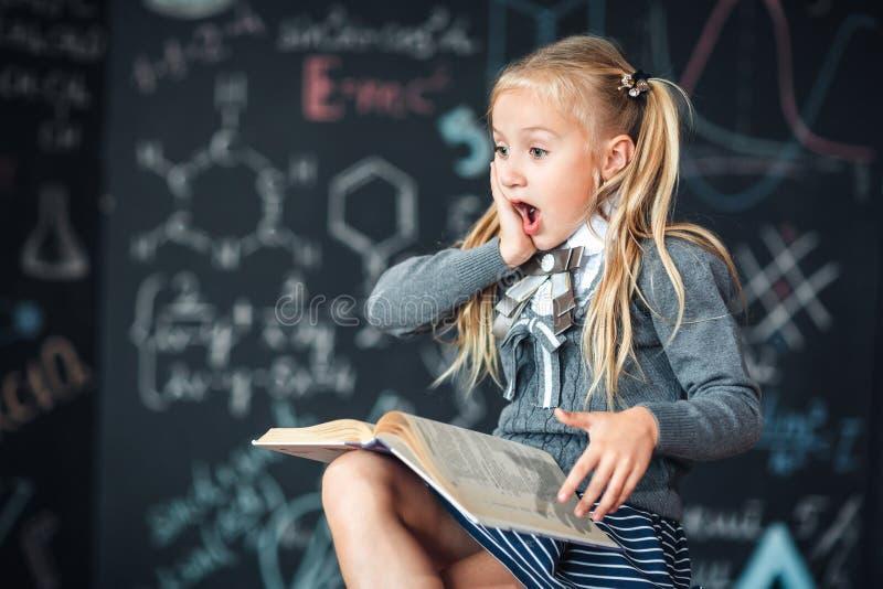 Ein süßes Mädchenschulmädchen sitzt auf einer Tafel mit Schulformelhintergrund Arbeitshausarbeit durch das Ablesen eines Buches ü stockfotos