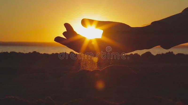 Ein Sand läuft Hände auf einem Sonnenunterganghintergrund durch stock video