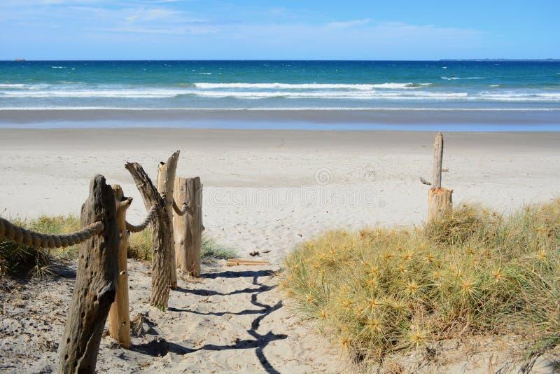 Ein sandiger steiler Fußweg, der zu das Meer führt; hölzerne Dekorationen auf einer Seite des Weges; schöner sonniger Tag und hel lizenzfreie stockfotografie