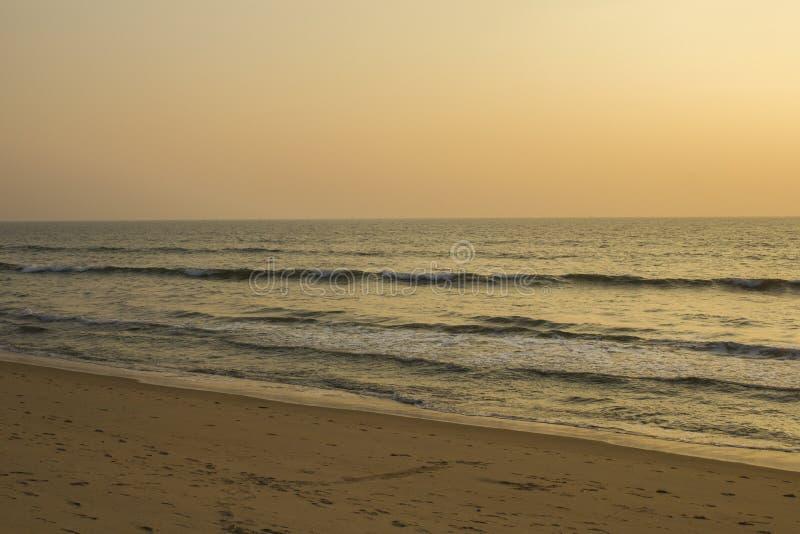 Ein sandiger Strand mit vielen Abdrücken auf dem Hintergrund der Wellen des Ozeans und des grauen rosa Himmels des Sonnenuntergan lizenzfreies stockfoto