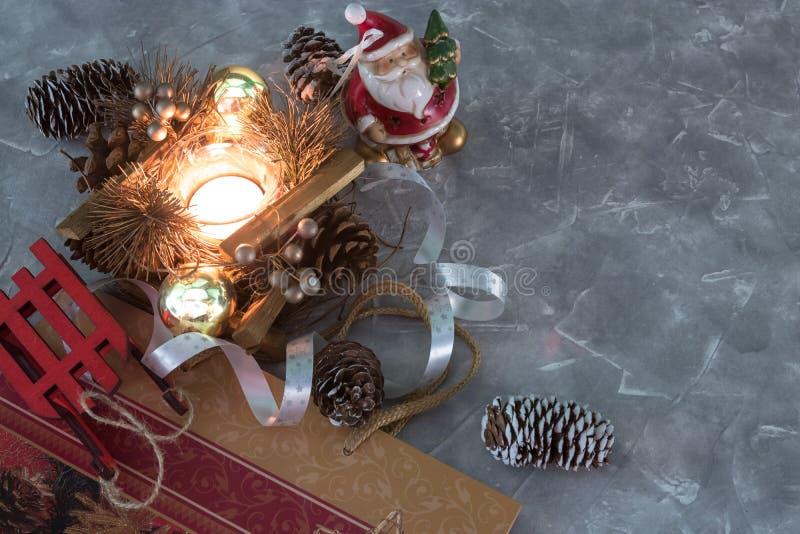 Ein Santa Claus-Spielzeug, eine brennende Kerze und ein Schlitten glückliches Mädchen mit Reisenfall Satz Weihnachtsdekorationen  lizenzfreie stockbilder
