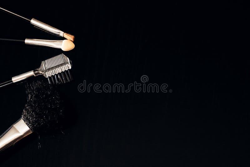 Ein Satz Bürsten für das Anwenden der Make-upnahaufnahme auf einem dunklen Hintergrund stockfotografie