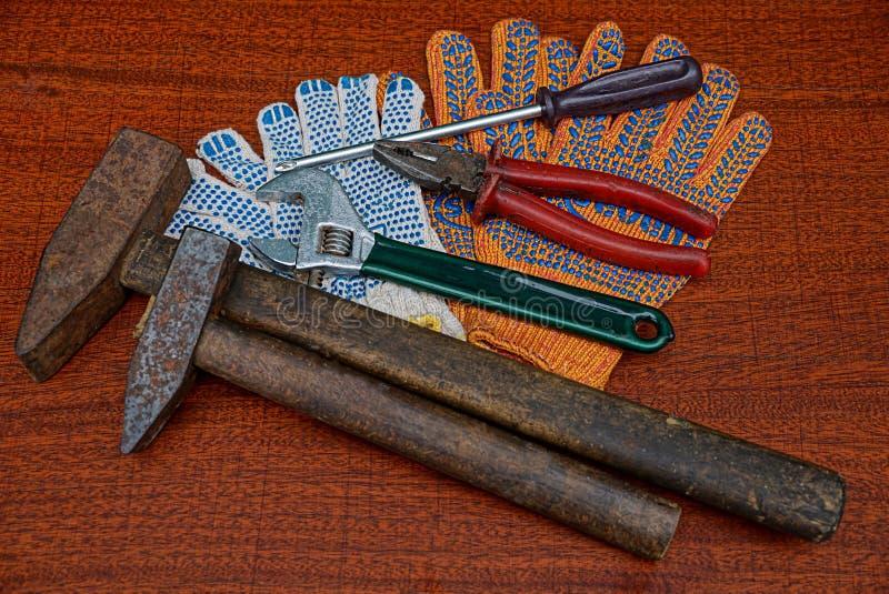 Ein Satz Bauwerkzeuge und Arbeitshandschuhe auf dem Tisch stockfoto