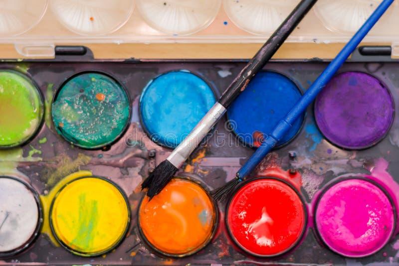 Ein Satz benutzte Aquarellfarben mit Bürstennahaufnahme lizenzfreie stockbilder